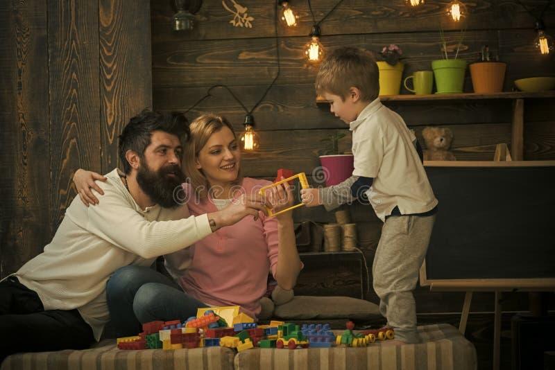 Οι γονείς αγκαλιάζουν ο ένας τον άλλον παίζοντας με το παιδί Πλάγια όψη που στέκεται το ξανθό αγόρι που παίρνει τις πλαστικές λεπ στοκ φωτογραφία