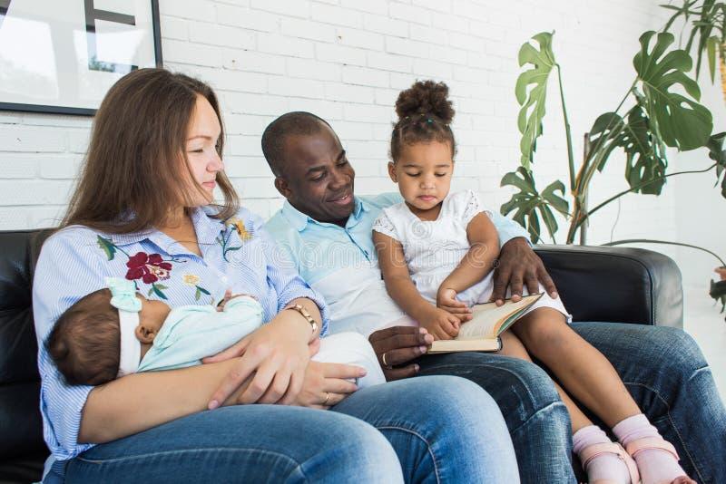 Οι γονείς διαβάζουν ένα βιβλίο στα παιδιά που κάθονται στον καναπέ Ευτυχής multiethnic οικογένεια Οικογενειακές αξίες στοκ εικόνα με δικαίωμα ελεύθερης χρήσης