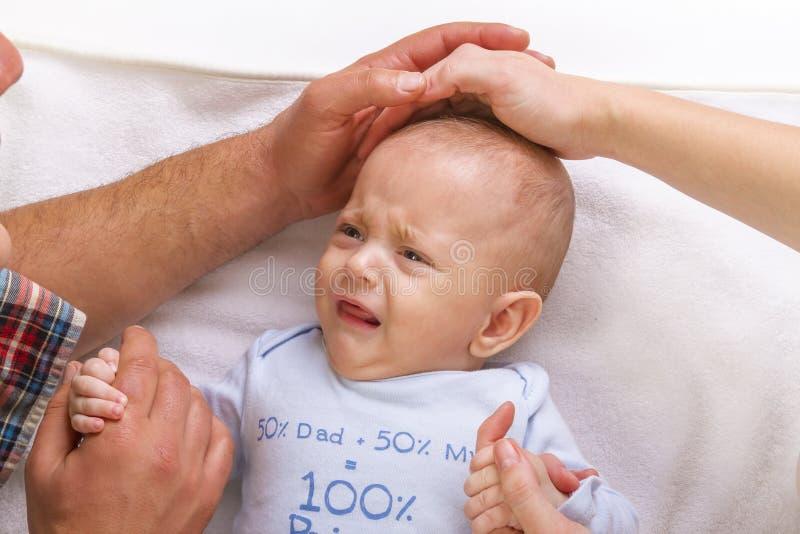 Οι γονείς ηρεμούν ένα φωνάζοντας μωρό στοκ εικόνες