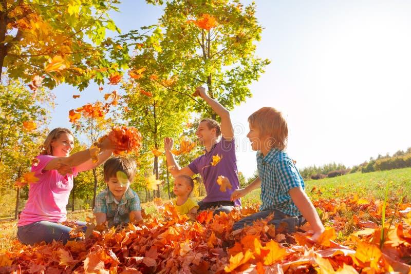 Οι γονείς και τα παιδιά ρίχνουν τα φύλλα στον αέρα από κοινού στοκ φωτογραφία με δικαίωμα ελεύθερης χρήσης