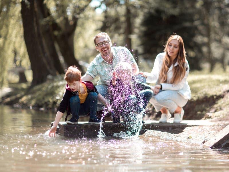 Οι γονείς με τα παιδιά χαλαρώνουν κοντά στη λίμνη στο πάρκο στοκ εικόνες