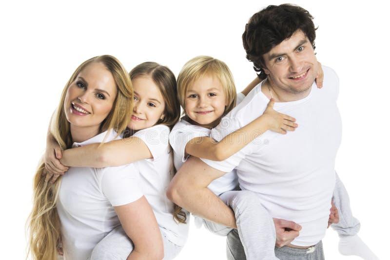 Οι γονείς που δίνουν τα παιδιά piggyback ο γύρος στοκ εικόνα με δικαίωμα ελεύθερης χρήσης
