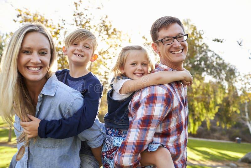 Οι γονείς που φέρνουν δύο νεαρούς τους piggyback σε ένα πάρκο στοκ εικόνες