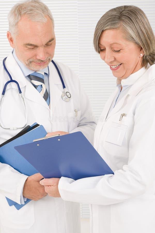 οι γραμματοθήκες γιατρών κρατούν τους ιατρικούς πρεσβυτέρους που χαμογελούν την ομάδα στοκ φωτογραφία