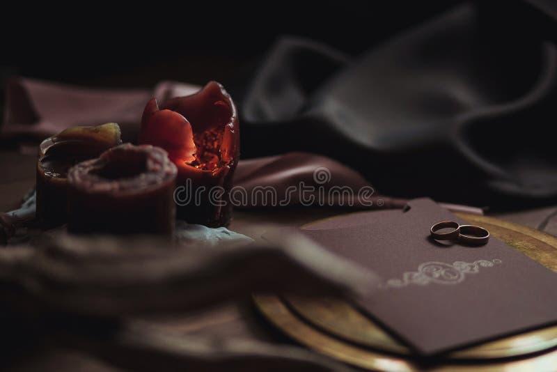 Οι γραφικές τέχνες των όμορφων γαμήλιων ροζ και καφετιών καρτών, χρυσό πιάτο με δύο δαχτυλίδια, σημαδεύουν τον καπνό, ύφασμα, εμπ στοκ φωτογραφία με δικαίωμα ελεύθερης χρήσης