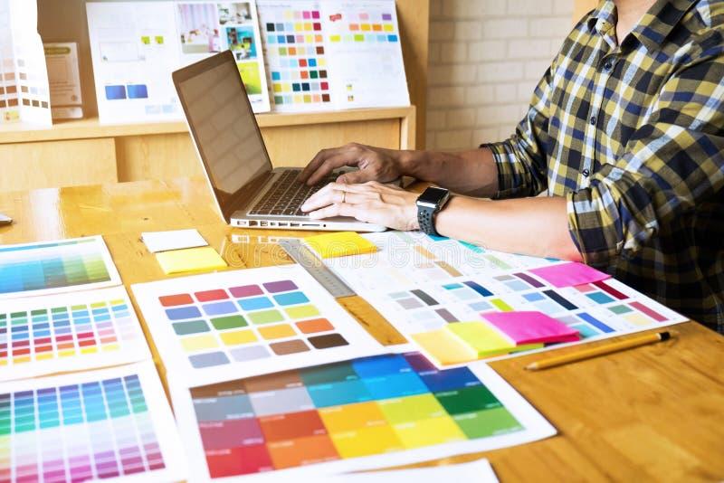 Οι γραφικοί σχεδιαστές χρησιμοποιούν το lap-top για να επιλέξουν τα χρώματα από το παράδειγμα φραγμών χρώματος για τις ιδέες σχεδ στοκ εικόνες