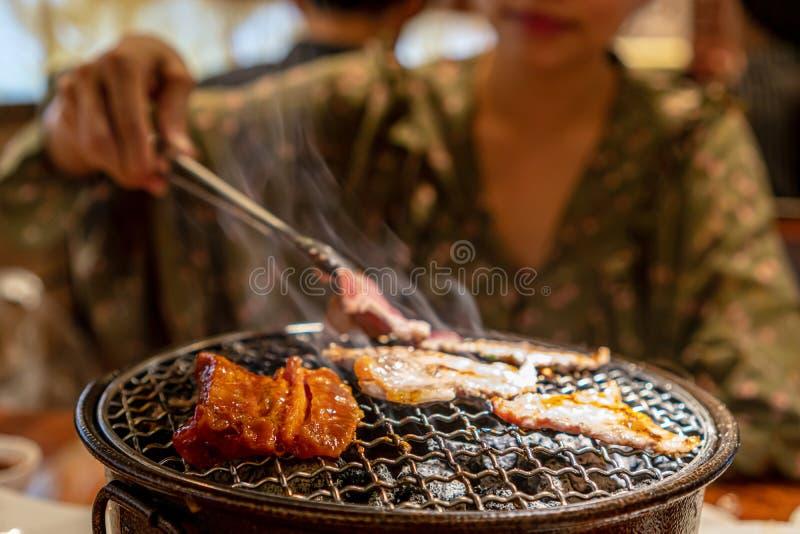 Οι γυναίκες έψησαν το ακατέργαστο χοιρινό κρέας πέρα από τη σόμπα ξυλάνθρακα στη σχάρα στοκ φωτογραφία με δικαίωμα ελεύθερης χρήσης