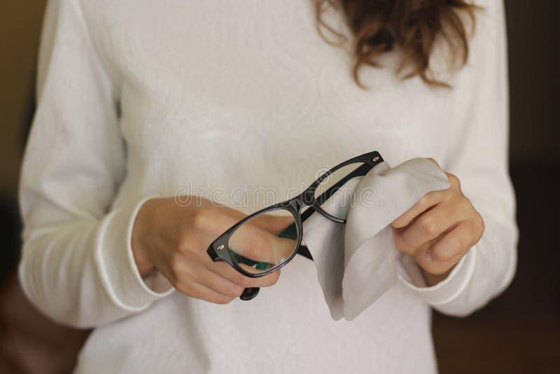 Οι γυναίκες δίνουν τον καθαρίζοντας φακό γυαλιών με το καφετί υπόβαθρο θαμπάδων στοκ φωτογραφίες με δικαίωμα ελεύθερης χρήσης
