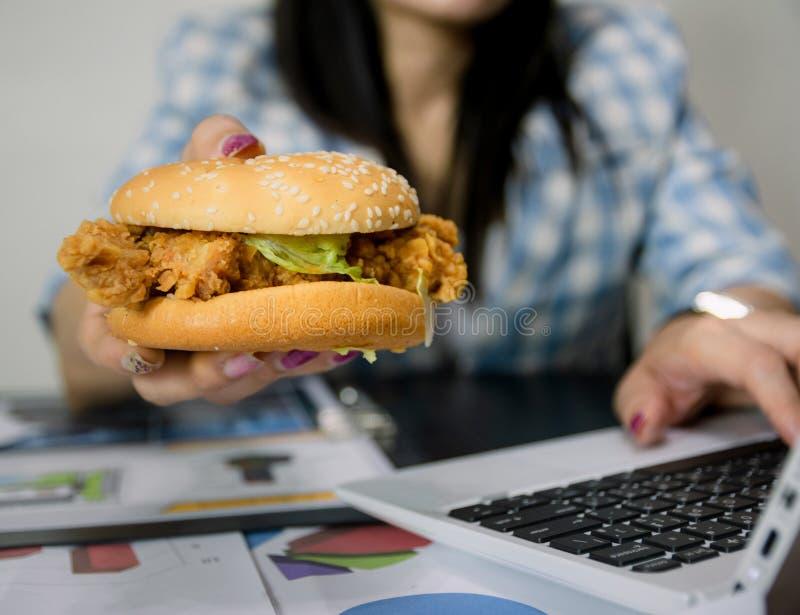 Οι γυναίκες απασχολούνται και τρώνε στα χάμπουργκερ για να φάνε το μεσημεριανό γεύμα στοκ εικόνες