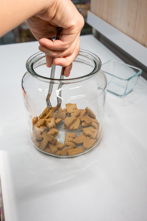 Οι γυναίκες δίνουν τη χρησιμοποίηση των ασημένιων λαβίδων μετάλλων για να επιλέξουν το μπισκότο αλφάβητου στοκ φωτογραφία με δικαίωμα ελεύθερης χρήσης