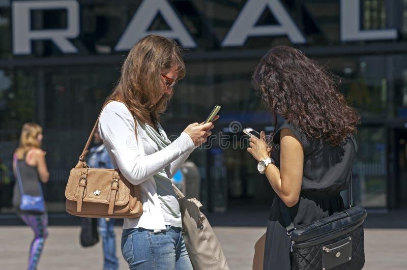 Οι γυναίκες επικοινωνούν με το smartphone ή το iPhone στοκ φωτογραφίες με δικαίωμα ελεύθερης χρήσης