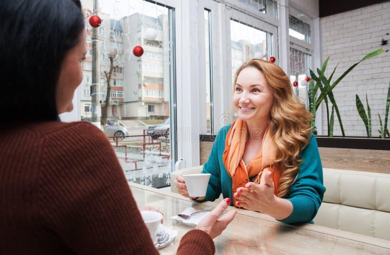 Οι γυναίκες κουτσομπολεύουν στον καφέ στοκ εικόνα