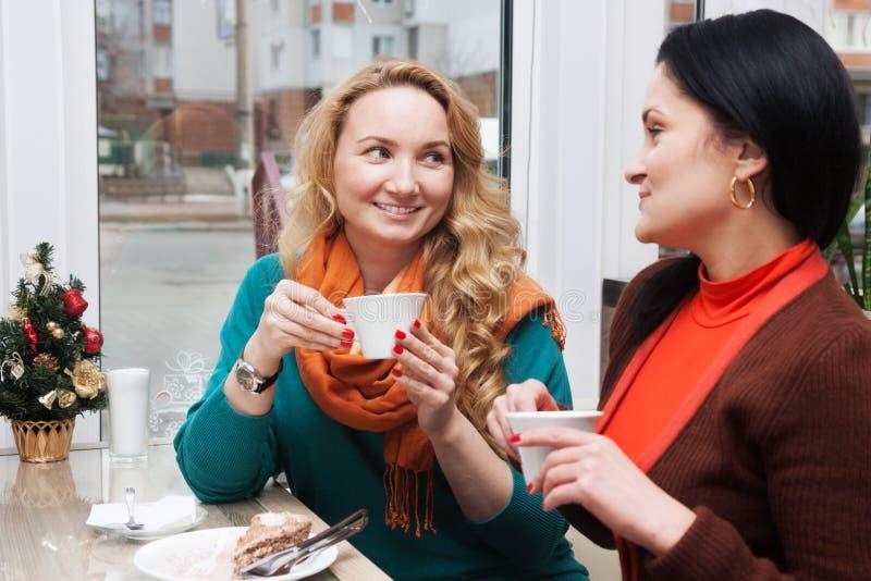Οι γυναίκες κουτσομπολεύουν στον καφέ στοκ φωτογραφίες