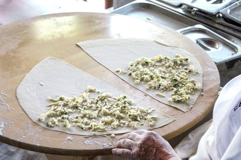 Οι γυναίκες μαγειρεύουν ένα τουρκικό pita ` gozleme ` με το τυρί και τα πράσινα στοκ φωτογραφία με δικαίωμα ελεύθερης χρήσης