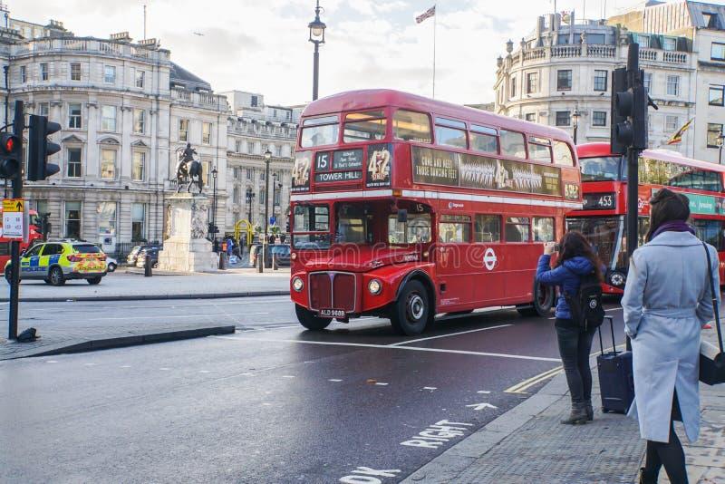 Οι γυναίκες με το μαλλί ντύνουν το σταυρό ο δρόμος μπροστά από τη πλατεία Τραφάλγκαρ με το κόκκινο λεωφορείο του Λονδίνου στοκ εικόνα