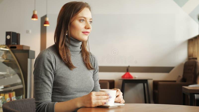 Οι γυναίκες πίνουν μια συνεδρίαση φλιτζανιών του καφέ στον καφέ στοκ φωτογραφία