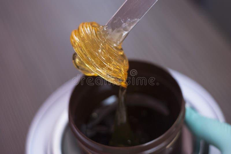 Οι γυναίκες παίρνουν έξω από το βάζο ζυμαρικά για έναν γλυκασμό, κίτρινο χρώμα Αποτριχωτική κόλλα ζάχαρης Ομορφιά και καλλυντικά στοκ εικόνες
