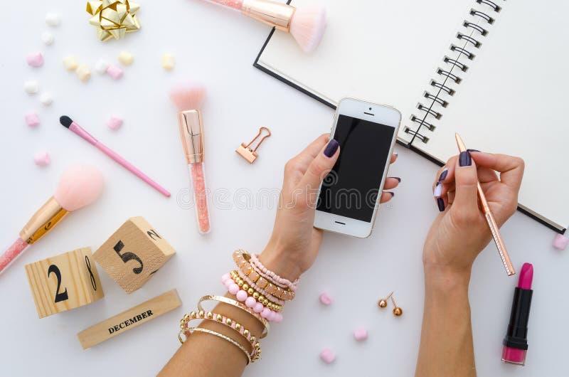 Οι γυναίκες παρουσιάζουν με marshmallow γλυκών, τις χρυσές προμήθειες γραφείων, τις ρόδινες βούρτσες makeup και το διαρκές ημερολ στοκ φωτογραφία με δικαίωμα ελεύθερης χρήσης