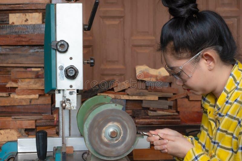 Οι γυναίκες που στέκονται είναι ακονίζουν το τρυπάνι σε έναν πάγκο εργασίας με τη μηχανή ακονών στοκ εικόνα