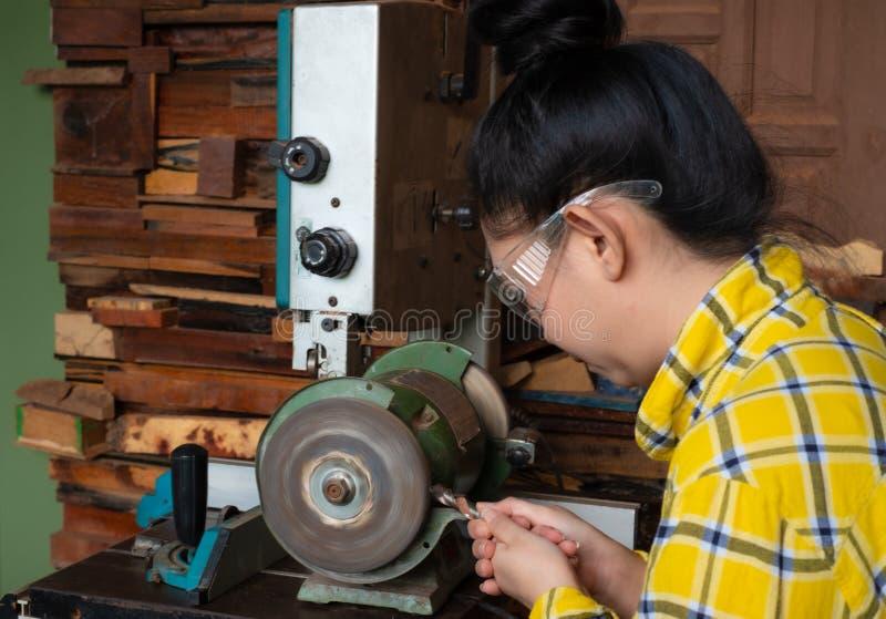 Οι γυναίκες που στέκονται είναι ακονίζουν το τρυπάνι σε έναν πάγκο εργασίας με τη μηχανή ακονών στοκ φωτογραφία με δικαίωμα ελεύθερης χρήσης