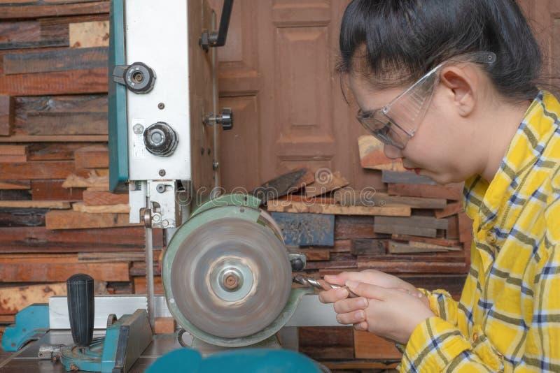 Οι γυναίκες που στέκονται είναι ακονίζουν το τρυπάνι σε έναν πάγκο εργασίας με τη μηχανή ακονών στοκ φωτογραφίες με δικαίωμα ελεύθερης χρήσης
