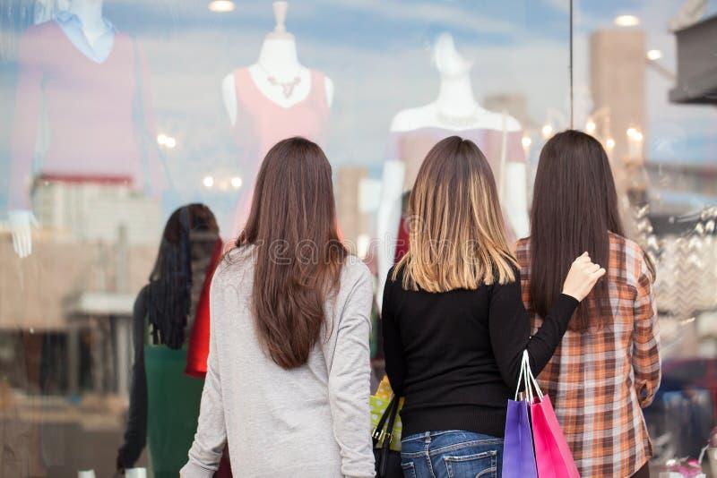 Οι γυναίκες που στέκονται μπροστά από έναν ιματισμό αποθηκεύουν στοκ εικόνες με δικαίωμα ελεύθερης χρήσης