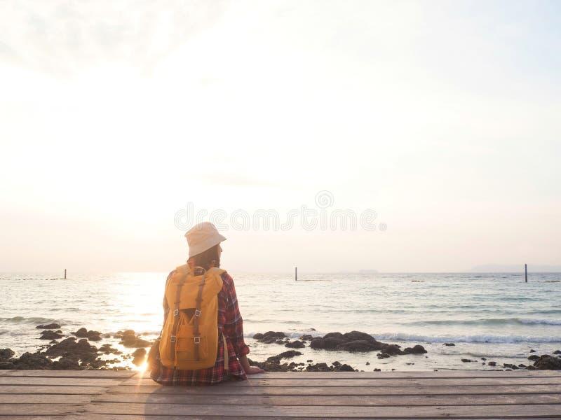 Οι γυναίκες που φορούν το κόκκινο πουκάμισο καρό και ένα κίτρινο σακίδιο πλάτης εξετάζουν τη θάλασσα σε ένα ξύλινο μπαλκόνι στοκ φωτογραφία