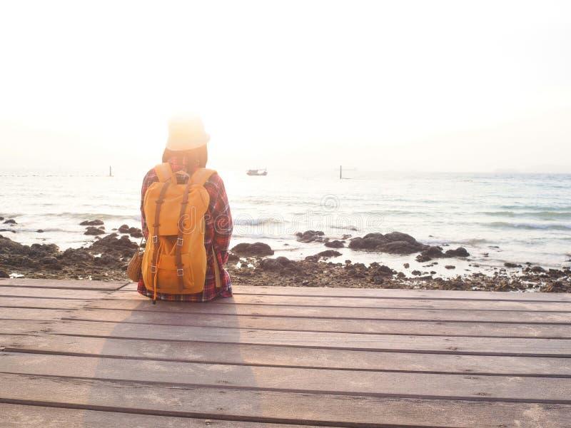Οι γυναίκες που φορούν το κόκκινο πουκάμισο καρό και ένα κίτρινο σακίδιο πλάτης εξετάζουν τη θάλασσα σε ένα ξύλινο μπαλκόνι στοκ φωτογραφίες