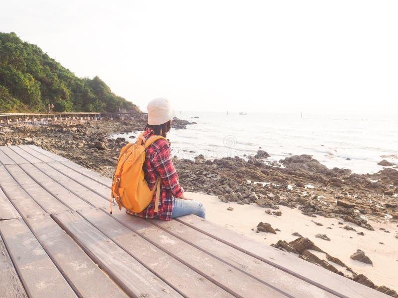 Οι γυναίκες που φορούν το κόκκινο πουκάμισο καρό και ένα κίτρινο σακίδιο πλάτης εξετάζουν τη θάλασσα σε ένα ξύλινο μπαλκόνι στοκ εικόνες με δικαίωμα ελεύθερης χρήσης