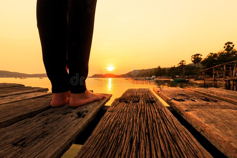 Οι γυναίκες στέκονται στο ξύλινο πάτωμα κοντά στη θάλασσα με το ηλιοβασίλεμα στοκ εικόνες