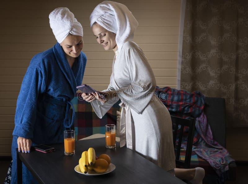 Οι γυναίκες στα εγχώρια ενδύματα πίνουν το χυμό στοκ φωτογραφία