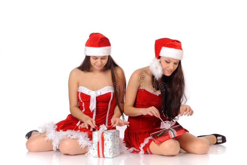 Οι γυναίκες στα κοστούμια Χριστουγέννων ανοικτά παρουσιάζουν στοκ φωτογραφία με δικαίωμα ελεύθερης χρήσης