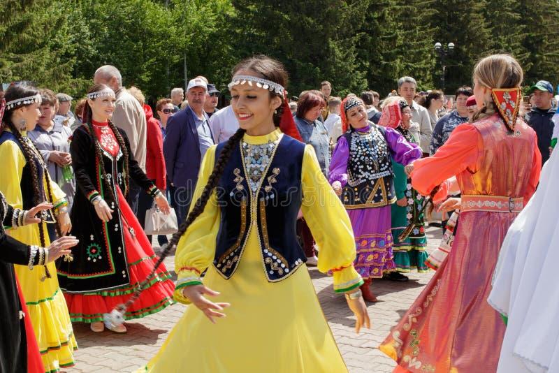 Οι γυναίκες στα Tatar εθνικά ενδύματα χορεύουν σε έναν κύκλο μεταξύ ενός πλήθους των ανθρώπων στοκ φωτογραφία με δικαίωμα ελεύθερης χρήσης