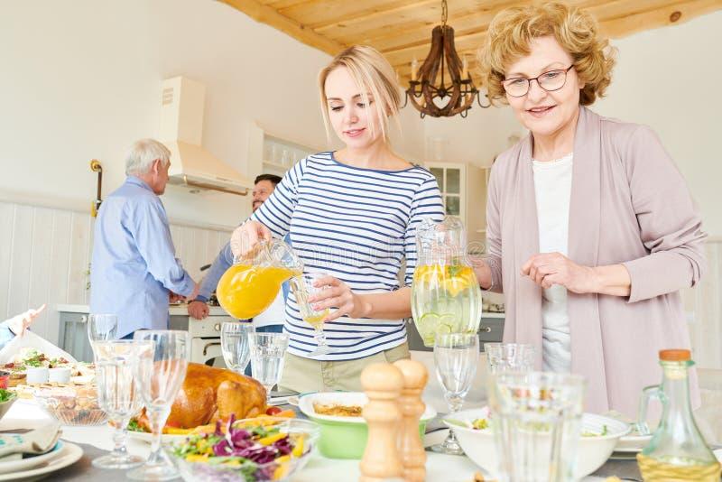 Οι γυναίκες του οικογενειακού θέτοντας γεύματος παρουσιάζουν στοκ φωτογραφία