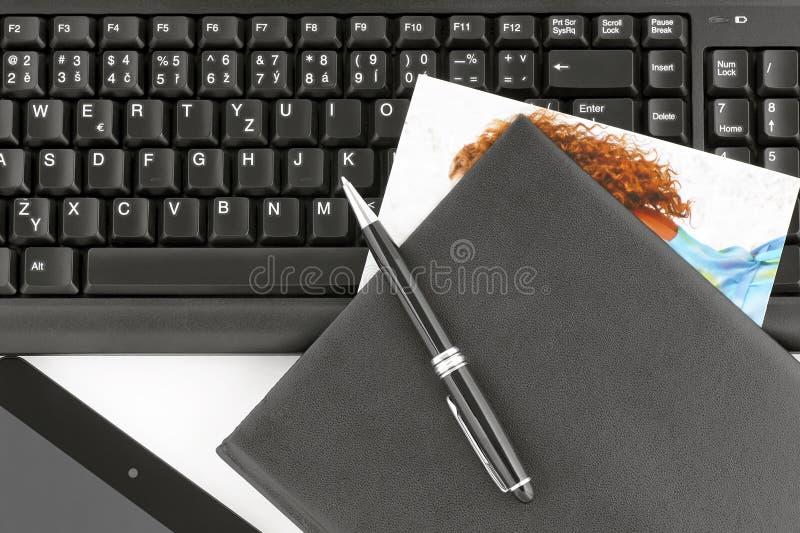 Οι γυναίκες φωτογραφιών παρενέβαλαν στο σημειωματάριο σε ένα πληκτρολόγιο υπολογιστών στοκ εικόνα με δικαίωμα ελεύθερης χρήσης