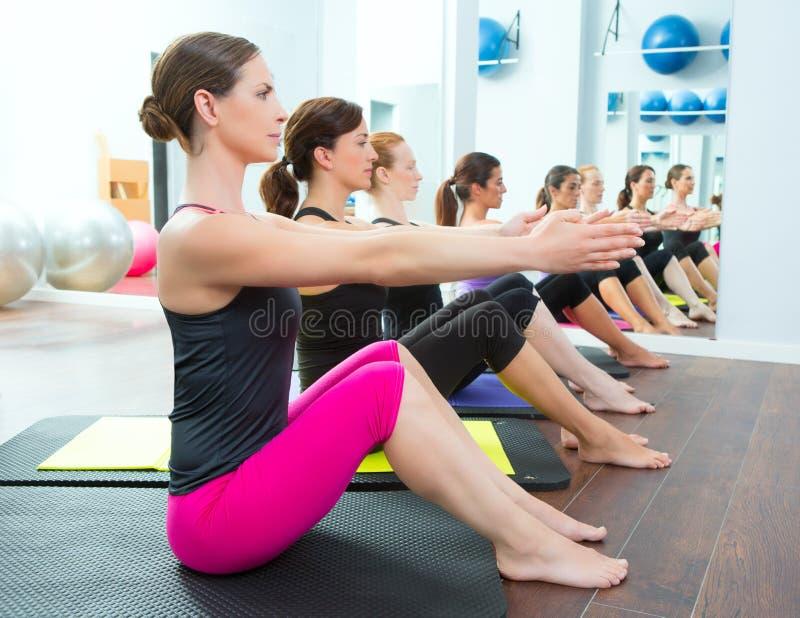 Οι γυναίκες Pilates ομαδοποιούν σχετικά με τον εκπαιδευτικό γυμναστικής χαλιών στοκ φωτογραφία
