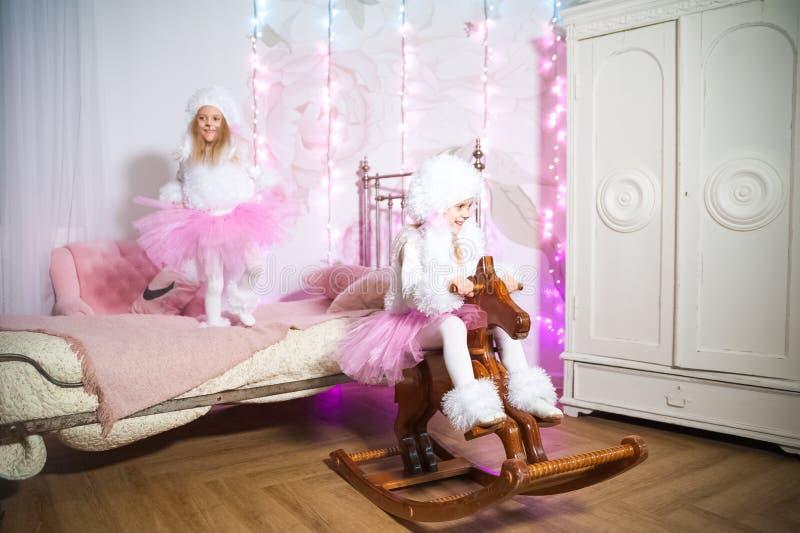 Οι δίδυμες αδελφές έντυσαν ως σκυλιά σε ένα δωμάτιο παιδιών ` s που διακοσμήθηκε για τα Χριστούγεννα Η αδελφή οδηγά ένα άλογο στο στοκ εικόνα