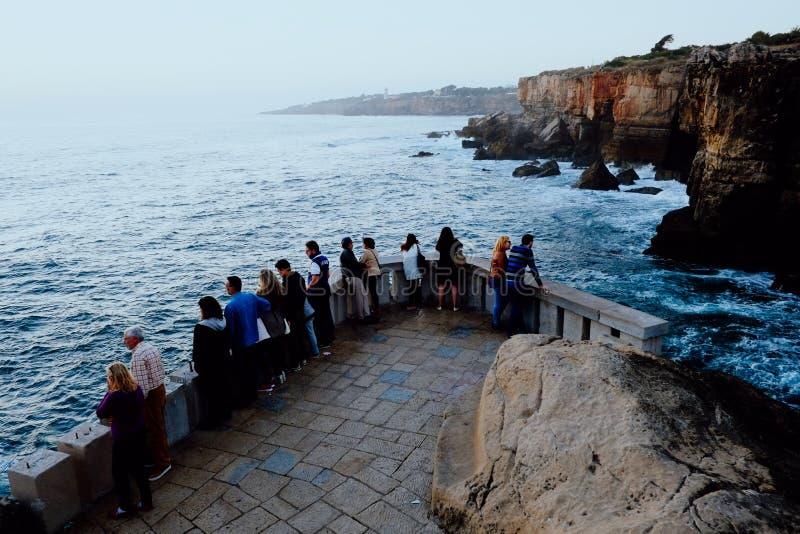 οι διάσημοι απότομοι βράχοι Boca do Inferno από την πλατφόρμα εξέτασης με τους τουρίστες στοκ φωτογραφία με δικαίωμα ελεύθερης χρήσης