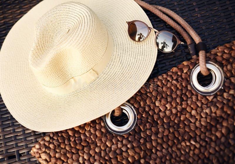Οι διακοπές, κλίση, ταξίδι, τρόπος ζωής και χαλαρώνουν την έννοια Καπέλο παραλιών, τσάντα Boho και γυαλιά θερινών ήλιων Εξαρτήματ στοκ φωτογραφία με δικαίωμα ελεύθερης χρήσης