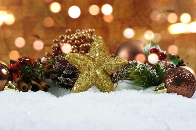 Οι διακοσμήσεις Χριστουγέννων και το αστέρι glittery στο χιόνι με το bok στοκ φωτογραφία