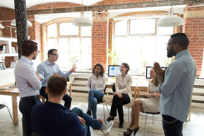 Οι διαφορετικοί συνάδελφοι έχουν τη διασκέδαση μιλώντας στο εκπαιδευτικό επιχειρησιακό trai στοκ εικόνες