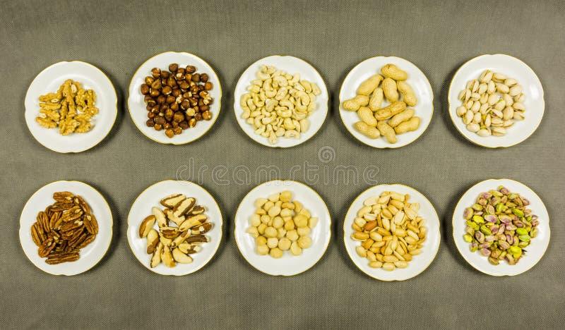 Οι διαφορετικοί τύποι ξεφλουδισμένων και unshelled καρυδιών παρουσιάζονται στα πιάτα επάνω από την όψη στοκ φωτογραφία με δικαίωμα ελεύθερης χρήσης