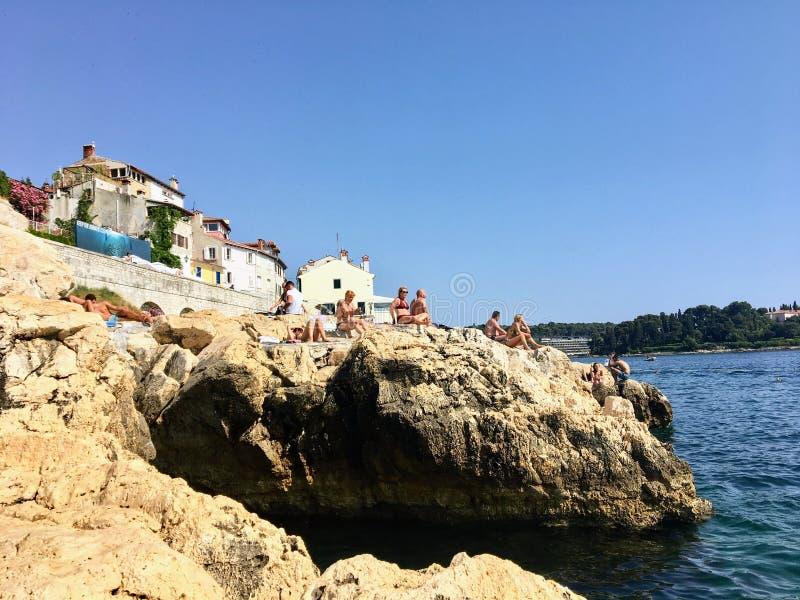 Οι δύσκολες ακτές της παλαιάς πόλης Rovinj, Κροατία κατά μήκος της αδριατικής θάλασσας Οι ντόπιοι και οι τουρίστες κολυμπούν στοκ εικόνες