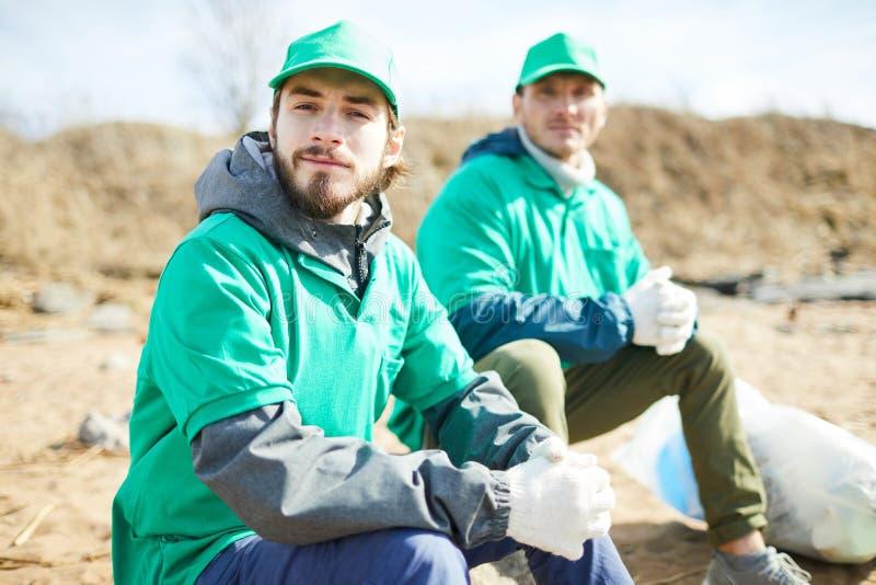 Οι εθελοντές που κάθονται στα σκουπίδια τοποθετούν σε σάκκο στοκ εικόνες