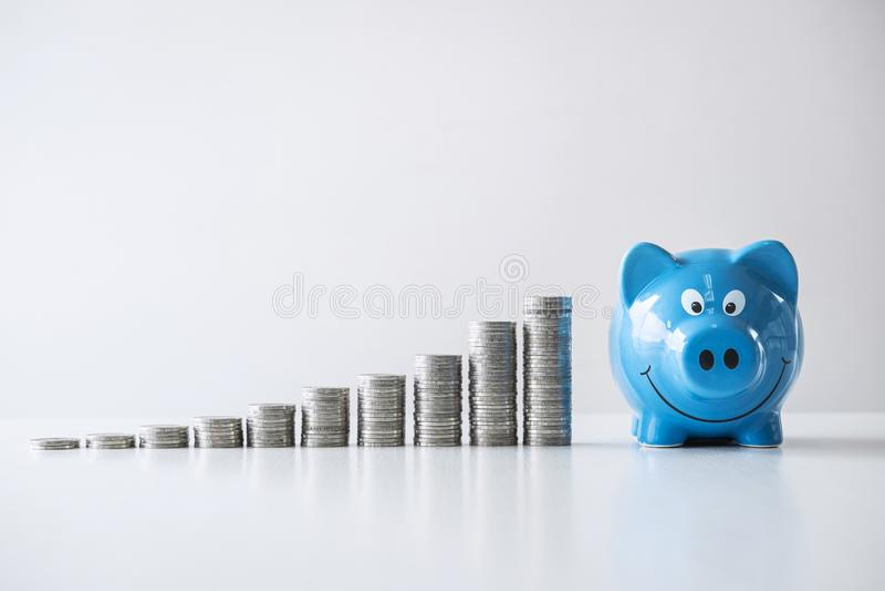 Οι εικόνες της συσσώρευσης των νομισμάτων συσσωρεύουν και μπλε χαμογελώντας τη piggy τράπεζα στην ανάπτυξη και την αποταμίευση με στοκ εικόνες