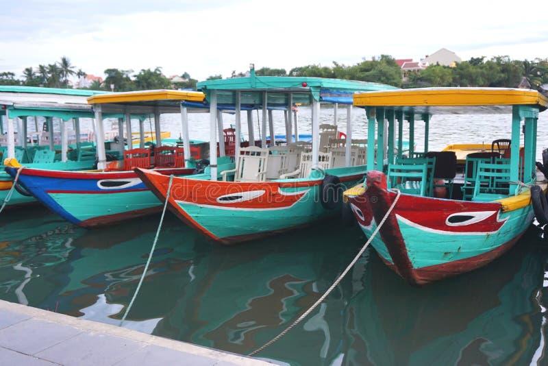 Οι εκλεκτής ποιότητας παραδοσιακές χρωματισμένες ξύλινες βάρκες γύρου έδεσαν κατά μήκος της αποβάθρας κοντά σε Hoi, Βιετνάμ στοκ φωτογραφία με δικαίωμα ελεύθερης χρήσης