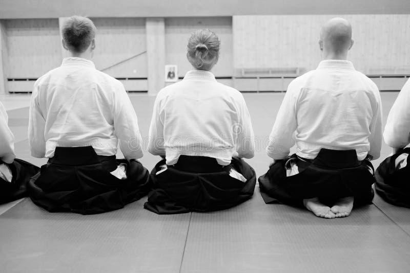 Οι εκπαιδευτικοί συμμετέχοντες Aikido κάθονται σε ένα χαλί στοκ φωτογραφία με δικαίωμα ελεύθερης χρήσης