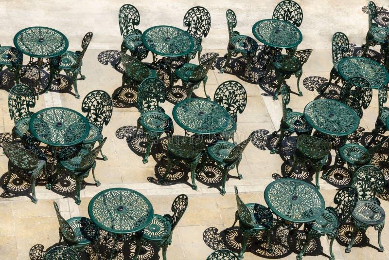 Οι εκλεκτής ποιότητας πράσινοι καρέκλες και οι πίνακες του καφέ οδών στοκ φωτογραφίες