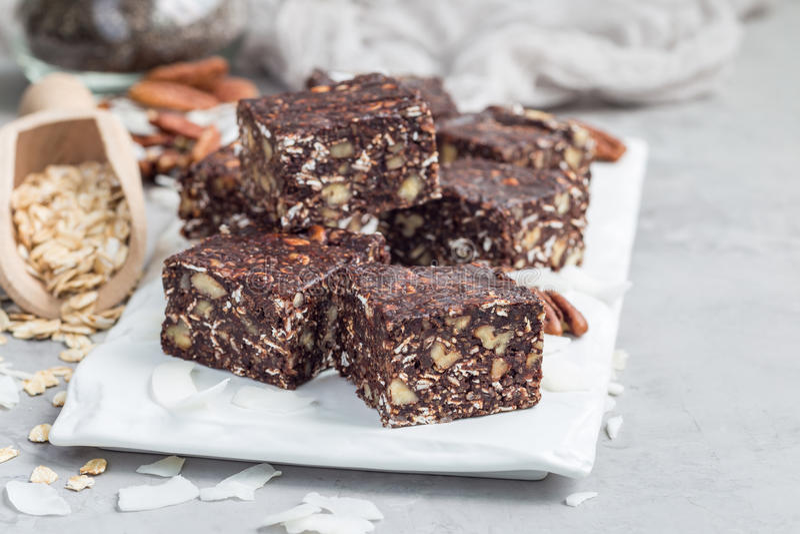 Οι ενεργειακοί φραγμοί σοκολάτας Paleo με τις κυλημένες βρώμες, τα καρύδια πεκάν, τις ημερομηνίες, τους σπόρους chia και την καρύ στοκ εικόνα με δικαίωμα ελεύθερης χρήσης