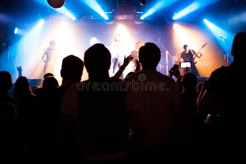 Οι ενθαρρυντικοί άνθρωποι συσσωρεύουν στη συναυλία παρουσιάζουν κατοχή της διασκέδασης και της επιδοκιμασίας μπροστά από τα φω'τα στοκ εικόνες με δικαίωμα ελεύθερης χρήσης